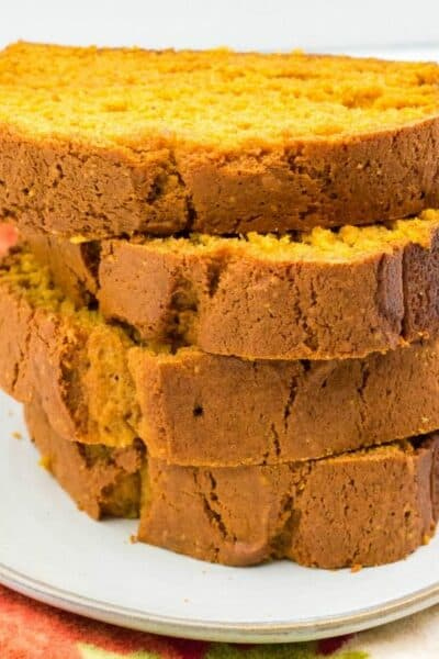 four slices of pumpkin bread stacked up on a white plate
