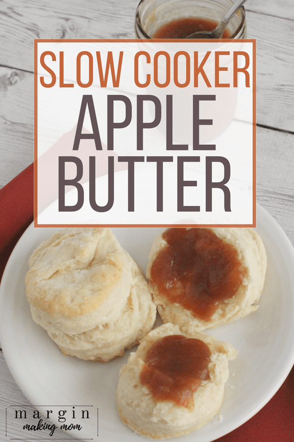 homemade biscuits topped with slow cooker apple butter, resting on a white plate