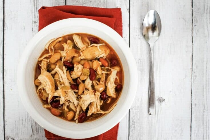 pressure cooker bbq chicken chili in a white bowl atop a red cloth napkin, next to a spoon