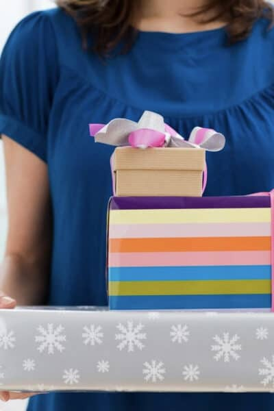 Woman in a blue shirt holding three wrapped gifts