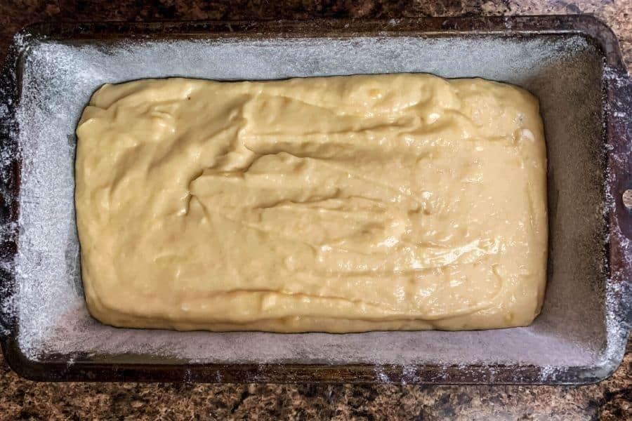 greased and floured loaf pan with banana bread batter in it