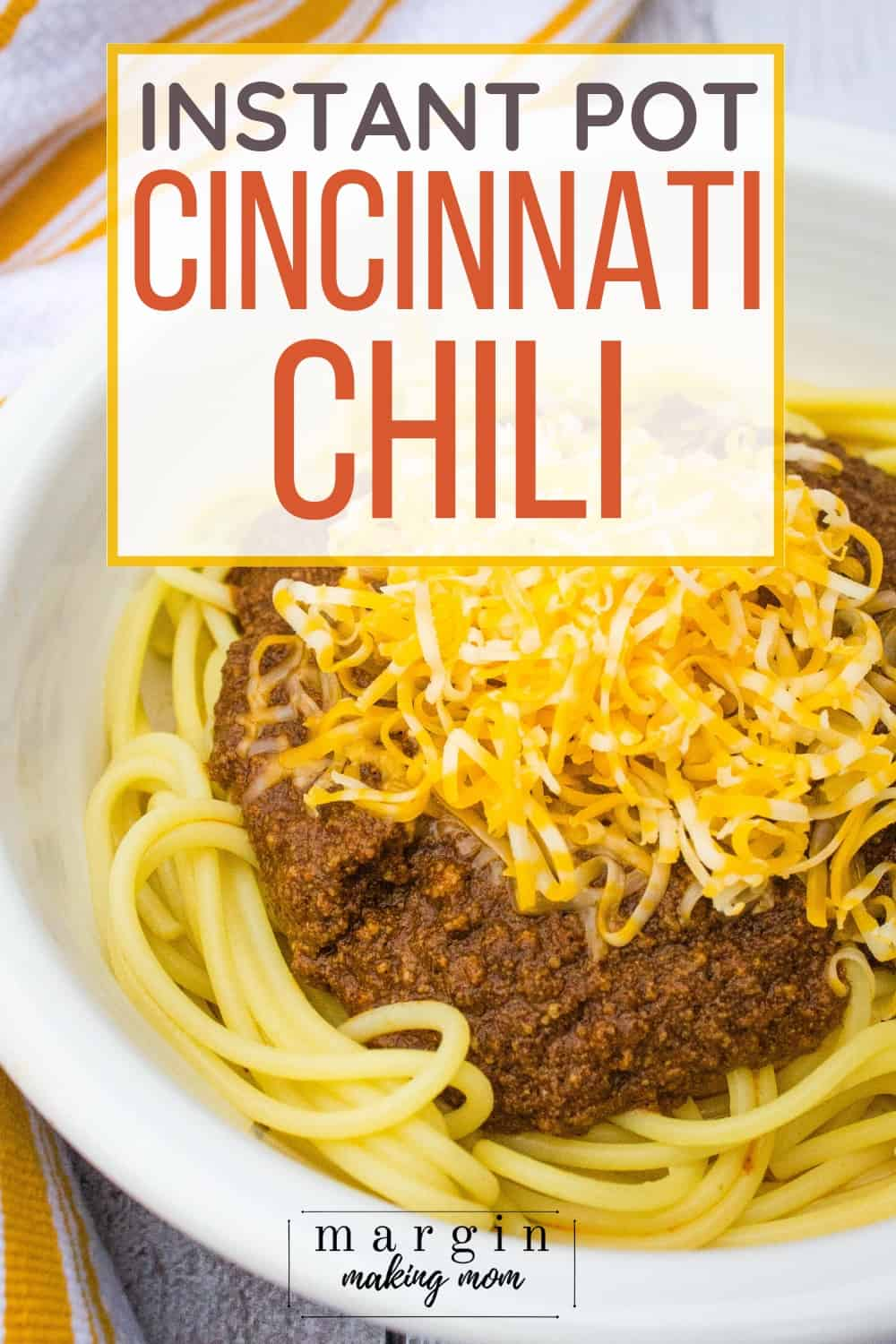 white bowl filled with spaghetti topped with Instant Pot Cincinnati Chili and shredded cheese