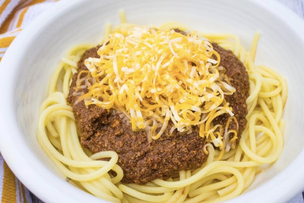 instant pot skyline chili topped with cheese and served over spaghetti in a white bowl