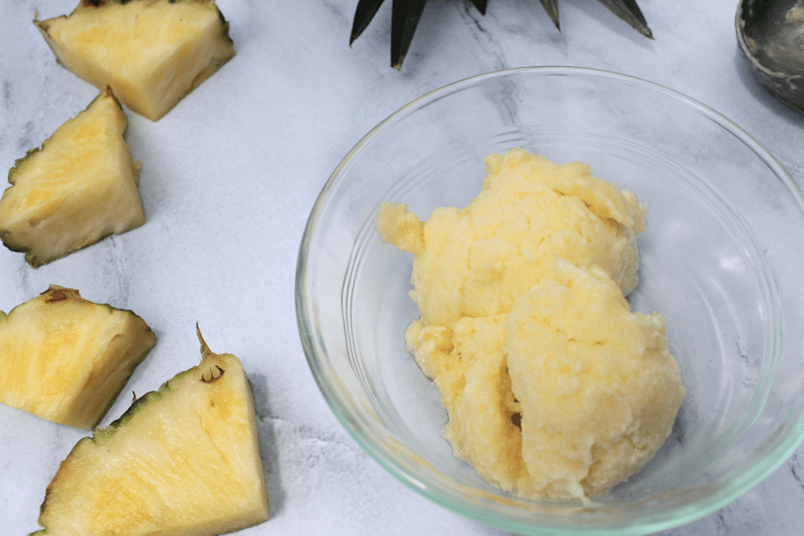 two scoops of pineapple sorbet in a glass bowl, next to slices of pineapple
