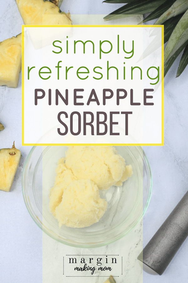 Two scoops of homemade pineapple sorbet in a glass bowl next to pieces of sliced pineapple