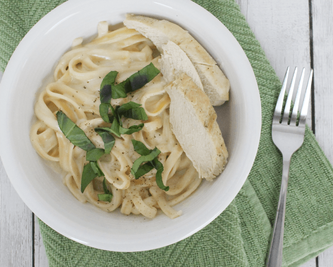 White plate with fettucine alfredo and sliced chicken breast, topped with fresh basil, all resting on a green napkin.