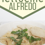 white bowl filled with chicken fettucine alfredo and topped with fresh basil
