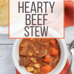 white bowl filled with pressure cooker beef stew, sitting on top of an orange cloth napkin