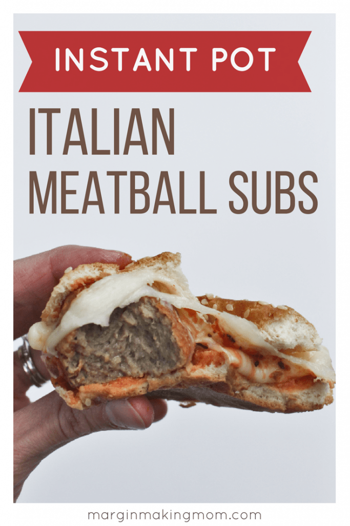 Hand holding an Italian meatball sub that has been bitten into