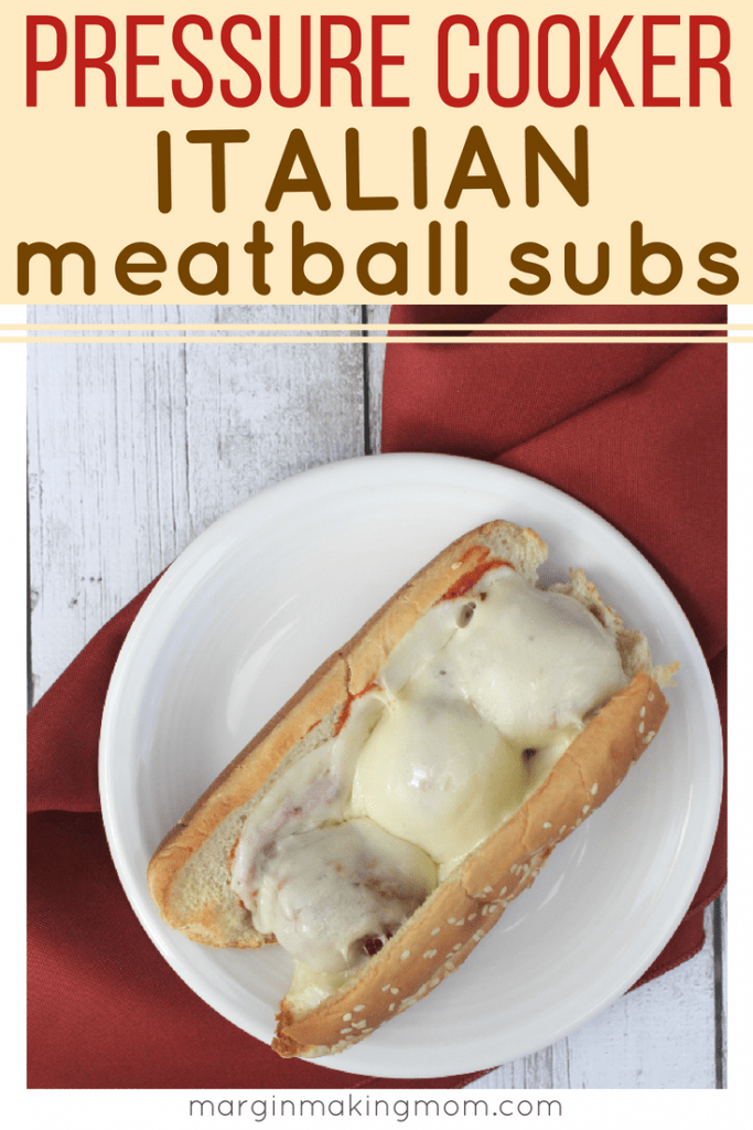 white plate with an italian meatball sub on it