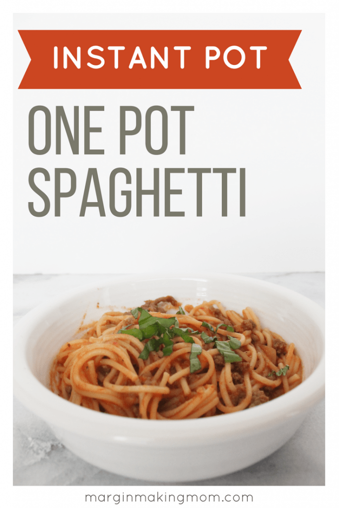 White bowl of spaghetti with meat sauce, topped with snipped basil