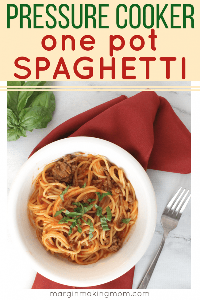 White bowl filled with spaghetti, resting on a red cloth napkin, next to a fork and a sprig of fresh basil