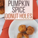 white plate with pumpkin spice donut holes on it, next to an orange cloth napkin