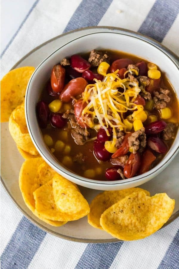 taco soup in a white bowl next to Fritos corn chips