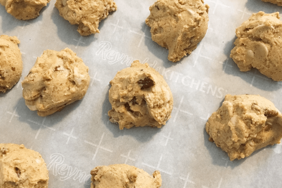 craggy surfaces of pumpkin pecan caramel chip cookies on a parchment lined baking sheet