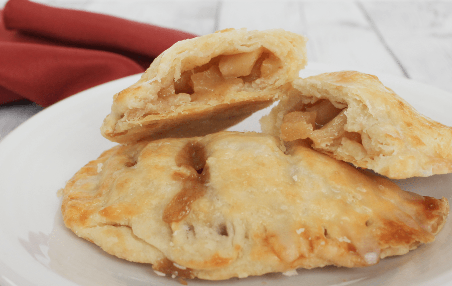 apple hand pies with filling exposed, resting on a white plate