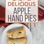 white plate topped with two apple hand pies, resting next to a red cloth napkin