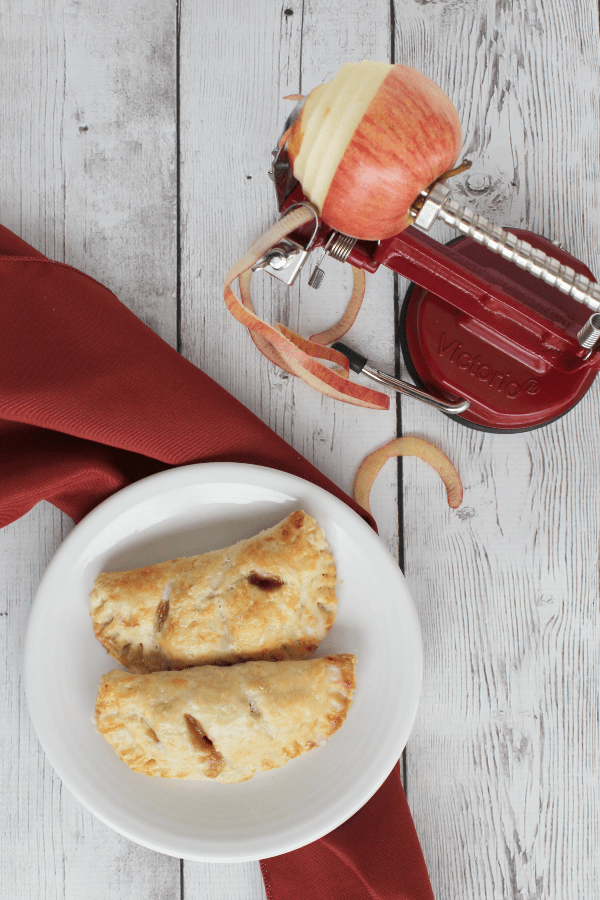 white plate with two apple hand pies resting on it, next to a red cloth napkin and a red apple peeler, slicer, and corer