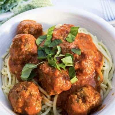 white bowl filled with spaghetti and homemade meatballs in a red sauce, topped with chopped basil