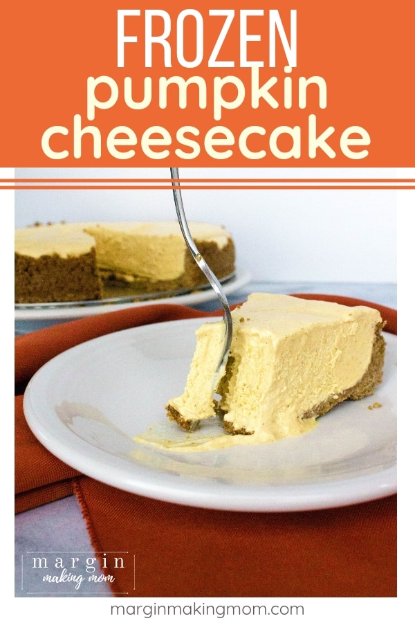 white plate with a piece of frozen pumpkin cheesecake on it, with a fork cutting out a bite of the cheesecake