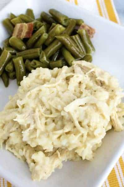 white plate with Instant Pot chicken and rice casserole on it, alongside green beans