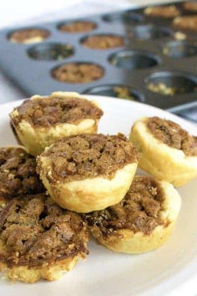 pecan pickups on a white plate with a muffin tin in the background