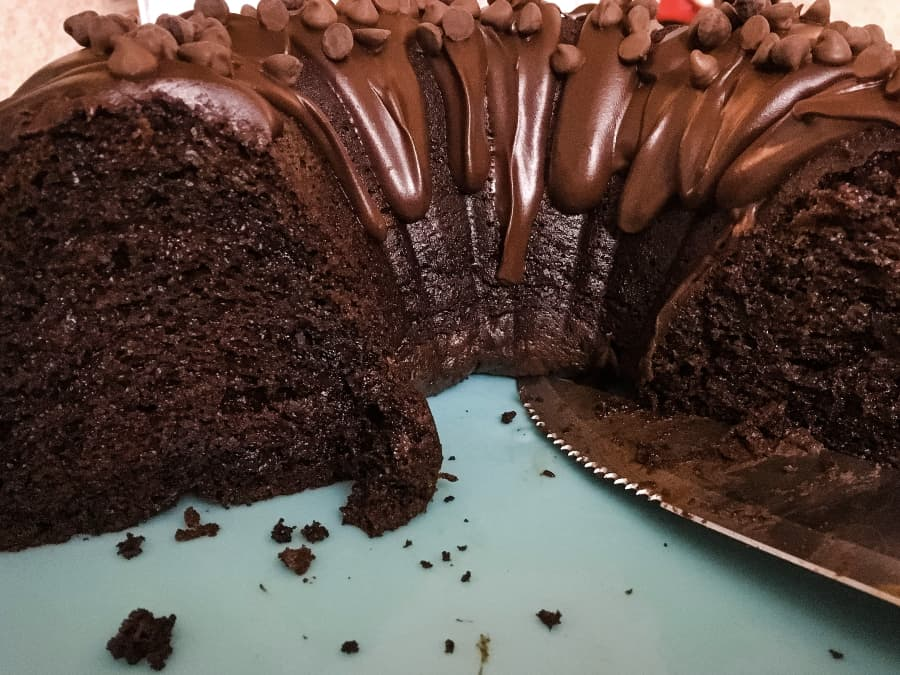 a cut chocolate bundt cake with glaze and chocolate chips on top, next to a knife