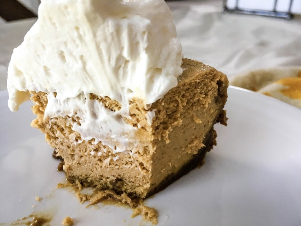 half-eaten piece of Pressure cooker pumpkin cheesecake, topped with whipped cream, sitting on a white plate