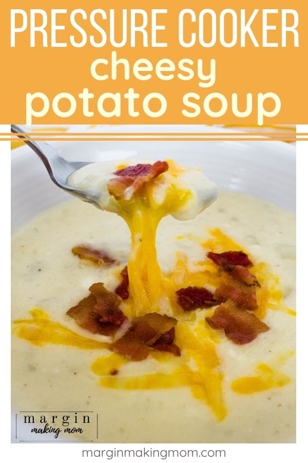 white bowl filled with instant pot potato soup, topped with bacon crumbles and melted cheese, with a spoon removing a bite of soup