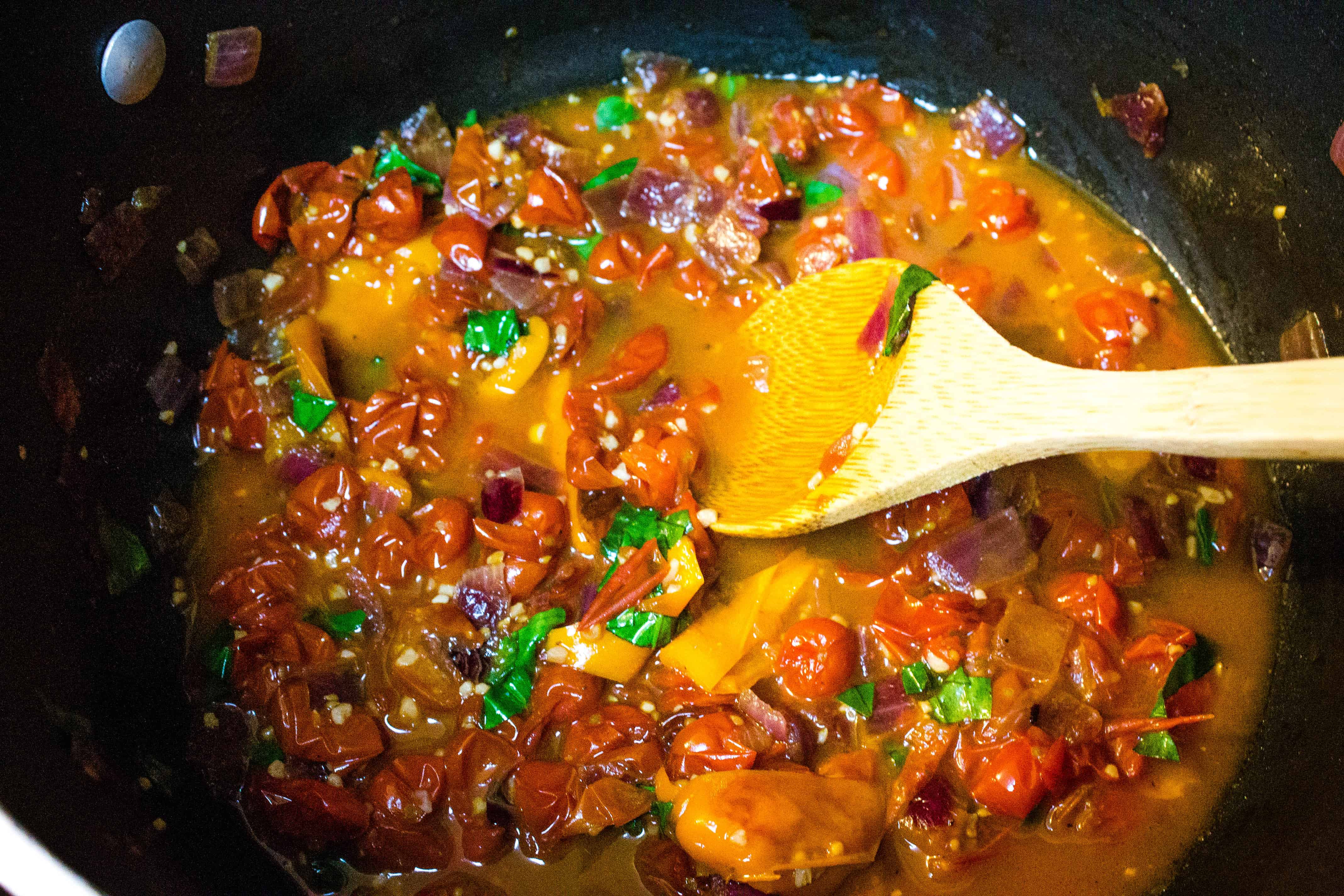 wooden spoon stirring roasted peppers and cherry tomatoes with onions, garlic, basil, and chicken broth to make cherry tomato sauce