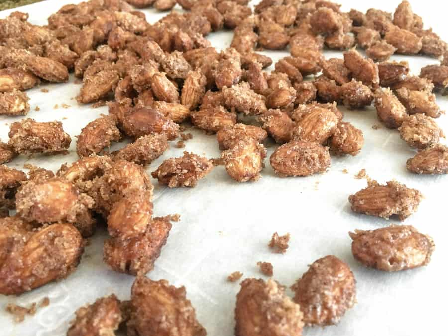 cinnamon sugar candied almonds cooling on a piece of parchment paper