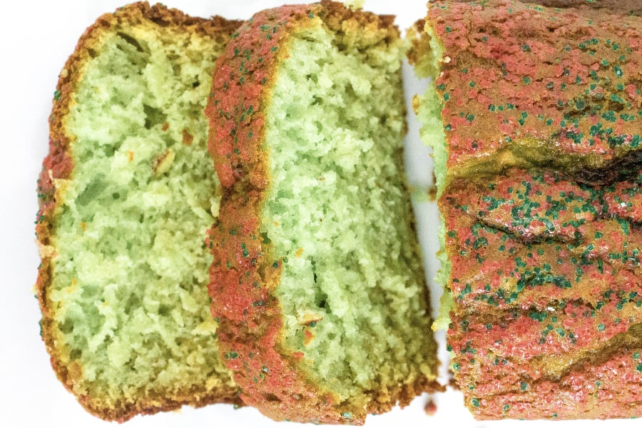 sliced loaf of pistachio bread with red and green sprinkles for christmas