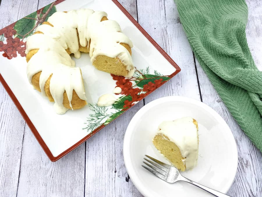 eggnog bundt cake on a holiday platter with one slice on a small white plate