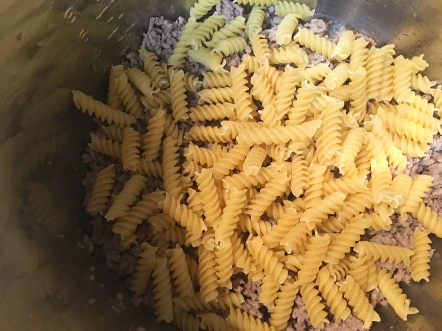 ground beef and pasta in the insert pot of an instant pot for enchilada pasta