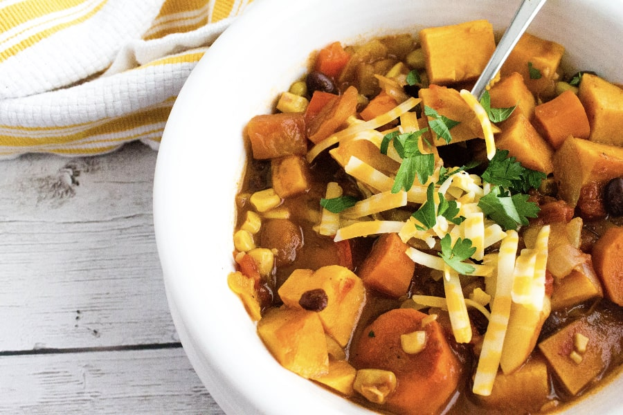 meatless vegetarian sweet potato chili made in the Instant Pot, served in a white bowl and topped with cheese
