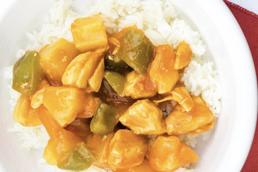 pressure cooker sweet and sour chicken over a bed of rice in a white bowl