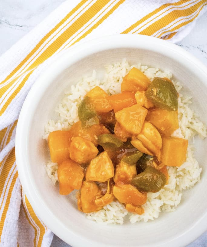 Instant Pot sweet and sour chicken over a bed of rice in a white bowl