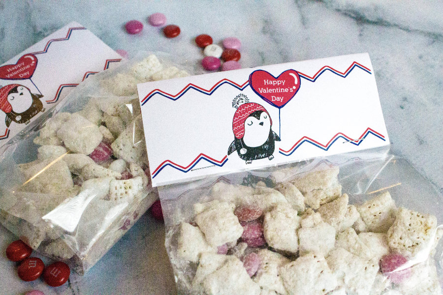 Valentine treat bags adorned with penguin bag toppers and filled with Valentine's snack mix