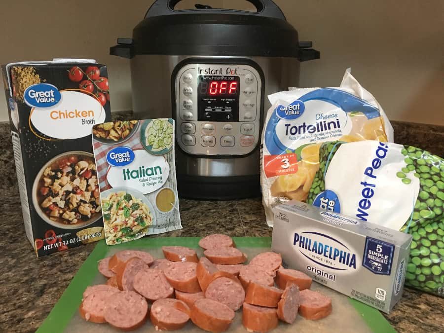 ingredients for Instant Pot creamy tortellini and sausage, including smoked sausage, frozen tortellini, chicken broth, Italian dressing mix, cream cheese, and frozen peas.