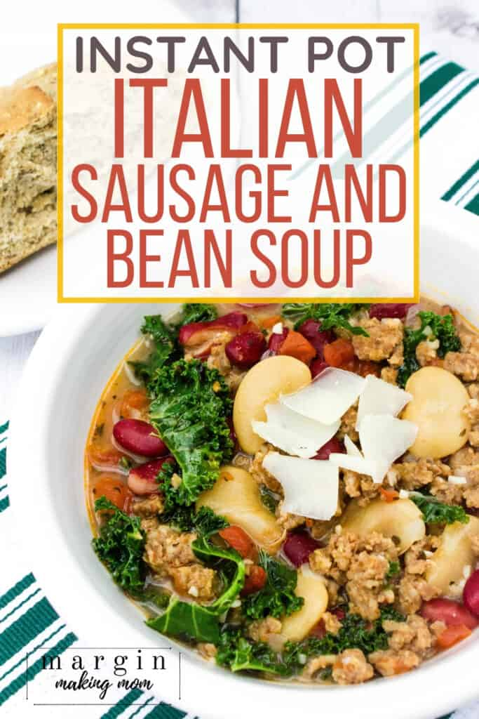 white bowl filled with Italian sausage and bean soup with kale and tomatoes, alongside a piece of crusty bread