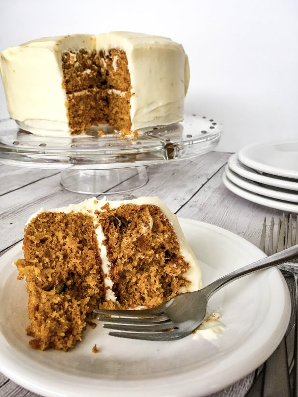 white plate with a piece of canned carrot cake with cream cheese frosting on it, with a fork alongside it