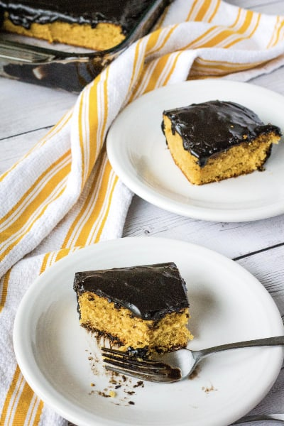 two white plates each with a piece of peanut butter cake with chocolate frosting, next to a yellow and white striped kitchen towel