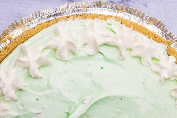 pistachio cream pie with graham cracker crust in an aluminum pie pan