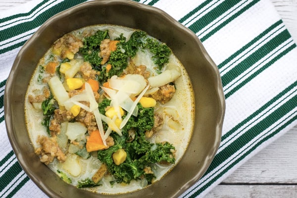 brown bowl filled with Instant Pot corn, sausage, and potato chowder; resting on a green and white striped cloth napkin