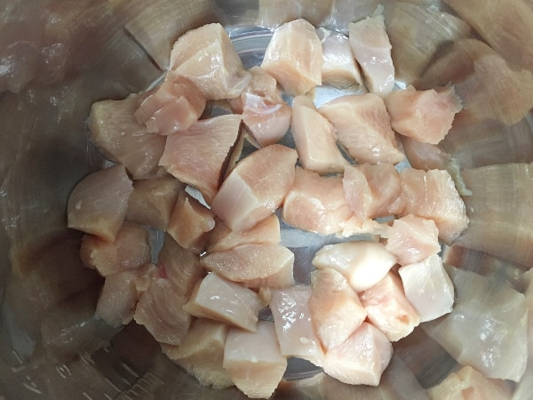 pieces of cut up chicken in the insert pot of the Instant Pot, for making Instant Pot bacon chicken ranch gnocchi