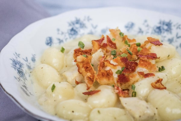 blue floral china bowl filled with pressure cooker bacon chicken ranch gnocchi