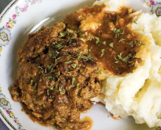 Instant Pot salisbury steak alongside mashed potatoes and gravy