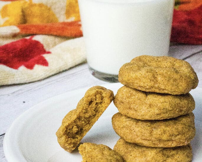 white plate with pumpkin snickerdoodles on it, next to a glass of milk