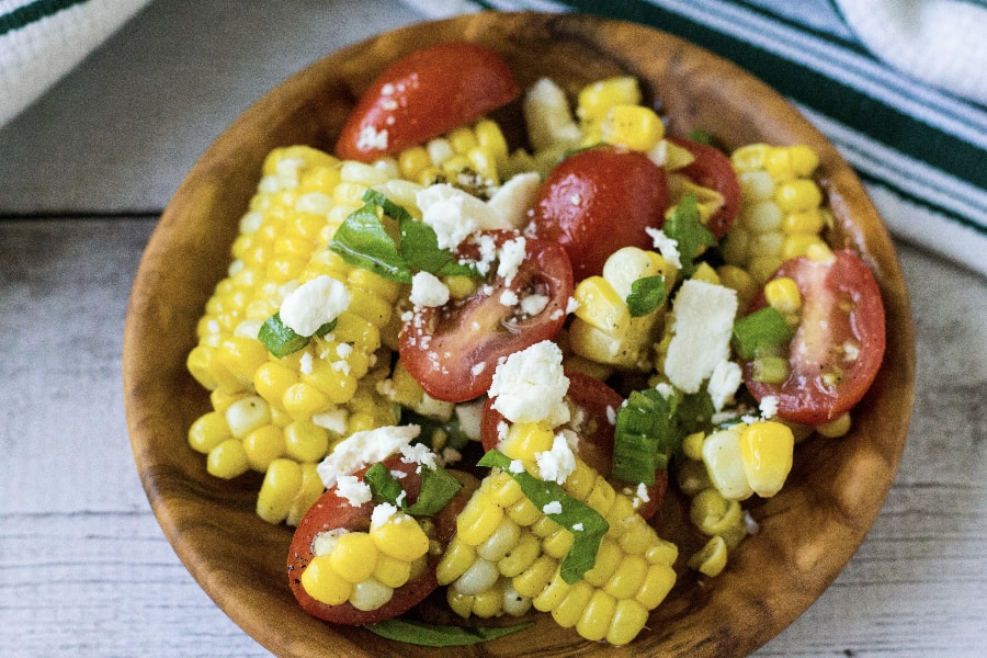wooden bowl filled with corn and tomato salad, made with corn cooked in the Instant Pot