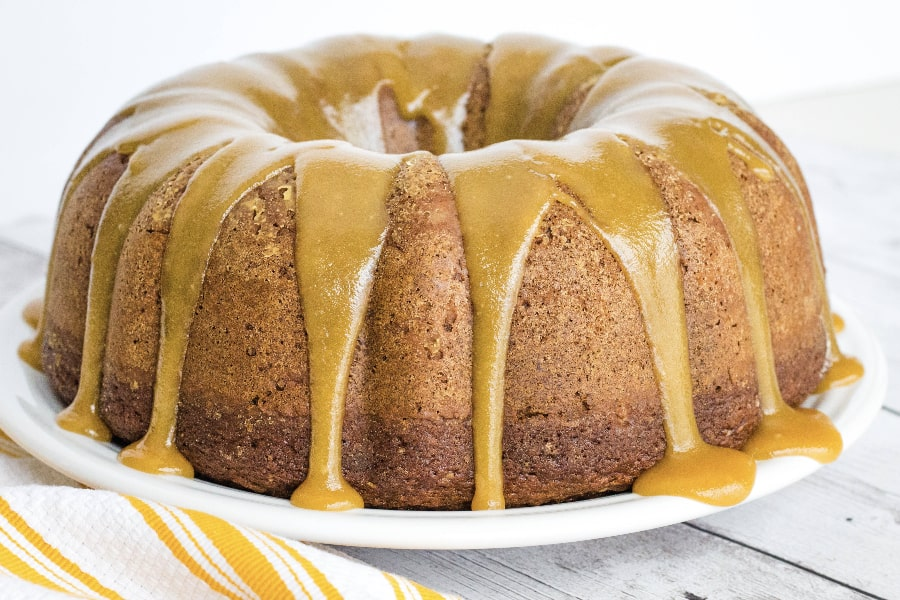 moist applesauce cake topped with caramel sauce on a white plate